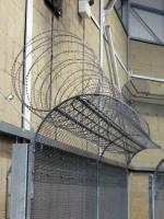 Utility fence toppings present razor wire only when climbed
